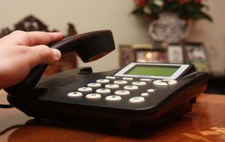 FOTOS DE UNA PERSONA HABLANDO POR UN TELEFONO FIJO, DETALLES DE UNA MANO MARCANDO UN NUMERO EN UN TELEFONO FIJO.